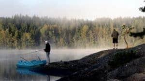 Det står en person och fiskar med ett kastspö. Det ligger dimma vid sjön.