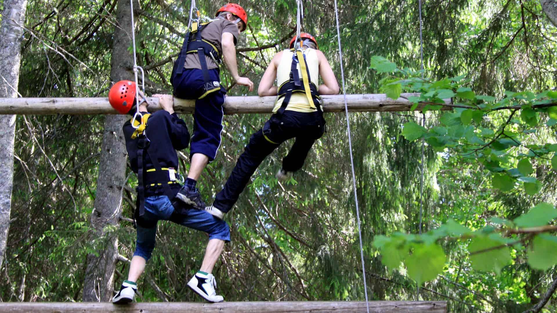 Tre personer klättrar i en jättrestor stege med stockar som hänger i vajrar.