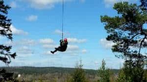 En person hänger i en jättelång vajer så det blir som en jättegunga.