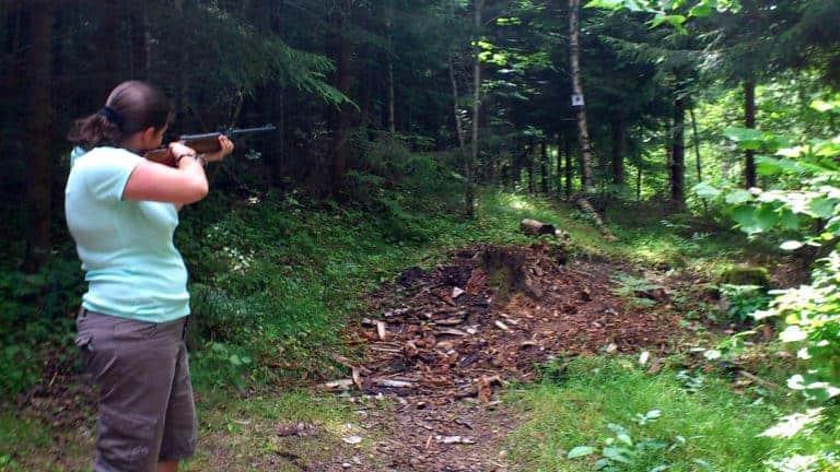 En kvinna skjuter luftgevär mot en tavla.