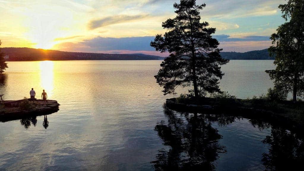 Två personer står på en udde vid en sjö. Det är en vacker solnedgång.