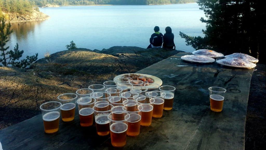Jättemånga glas med öl står på ett bord. Bordet står i naturen alldeles vid en sjö.