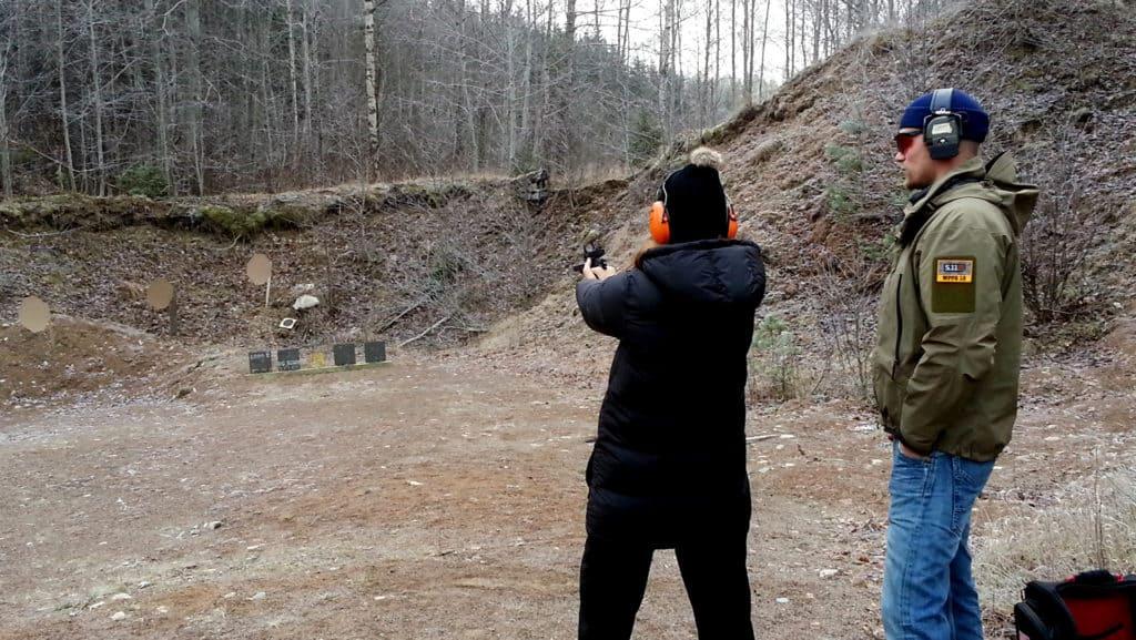 En person testar att skjuta pistol. En annan övervakar så han gör rätt.