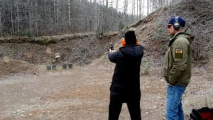 A person tests to shoot the pistol. Another monitors so he does right.
