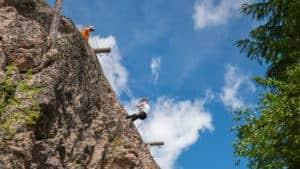En man tar sig ner för ett berg med hjälp av rep.