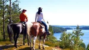Två personer som sitter på var sin häst står på ett berg. I bakgrunden syns en vacker sjö.