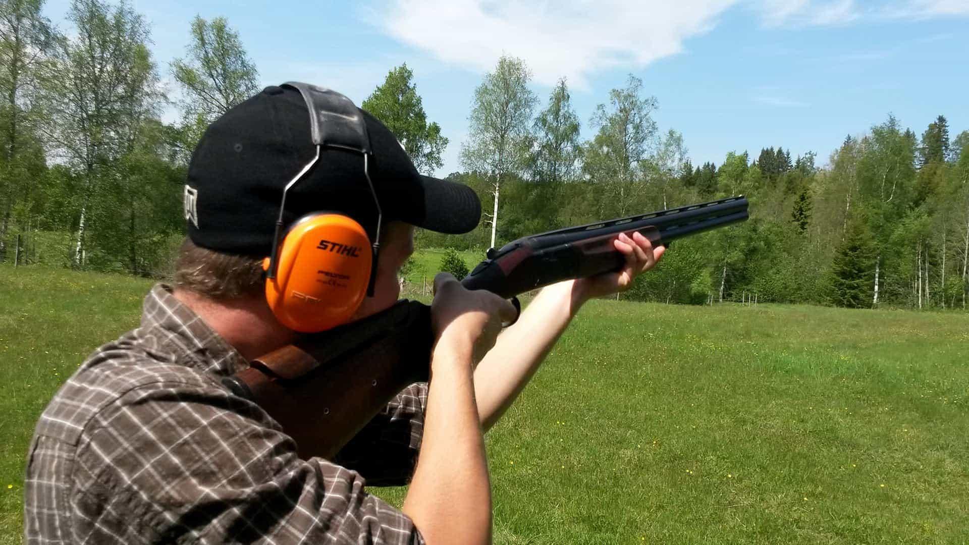 En man står med ett gevär och skjuter lerduva