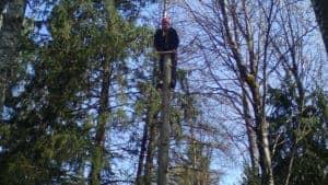 En person klättrar upp för en 10 meter hög stolpe som han skall hoppa från. Han sitter fast i rep på ryggen.
