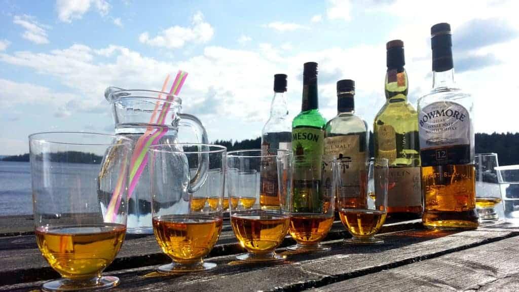 Whiskeyflaskor och glas står på ett bord. Sjön syns i bakgrunden.