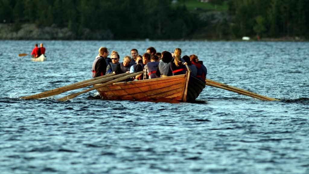 Många människor ror en kyrkbåt.